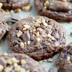 Deep, dark chocolate brownie cookies loaded with chocolate chunks and milk chocolate toffee bits. Crackly tops, fudgy centers, and chewy edges.