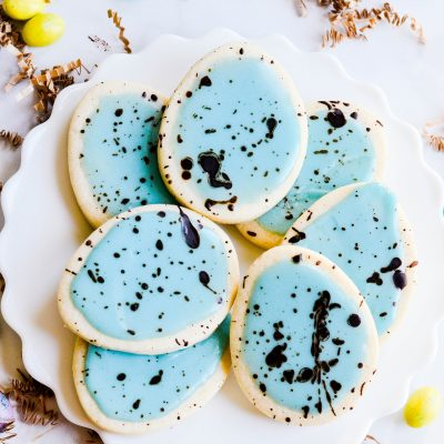 Soft cut-out sugar cookies that hold their shape, simple icing, and a cocoa splatter that makes these Easter Egg Sugar Cookies look speckled!