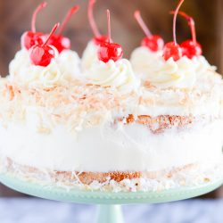 Extra moist pineapple coconut cake with a sweet vanilla-coconut buttercream and a toasted coconut topping.