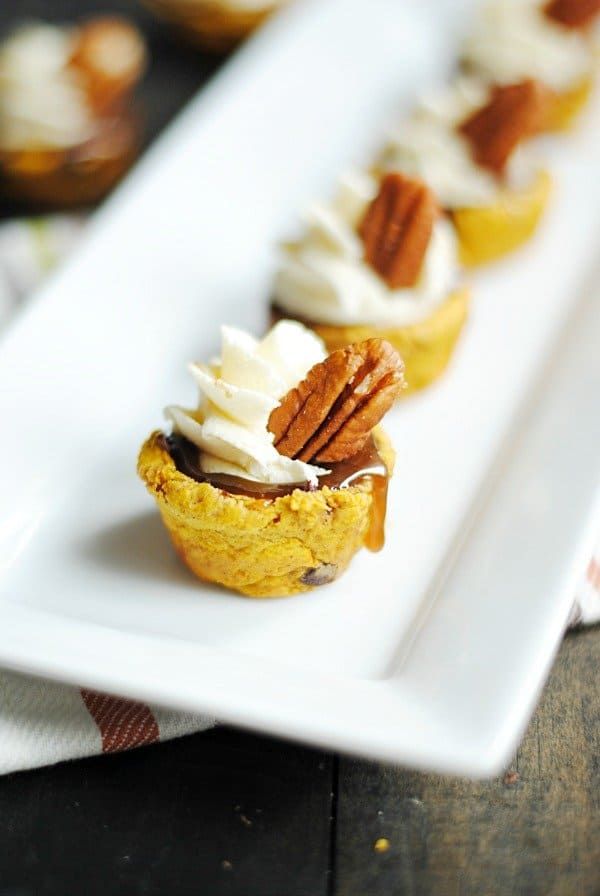 Pumpkin Chocolate Chip Cookies pressed into cups holding homemade salted caramel sauce and cheesecake buttercream! Delicious, impressive, and perfect for Fall!