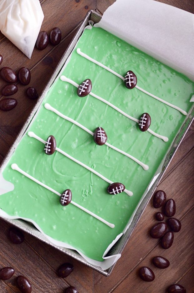 Easy to make delicious vanilla fudge that looks like a football field, with cute little chocolate covered almond footballs. This is the perfect treat for football parties!