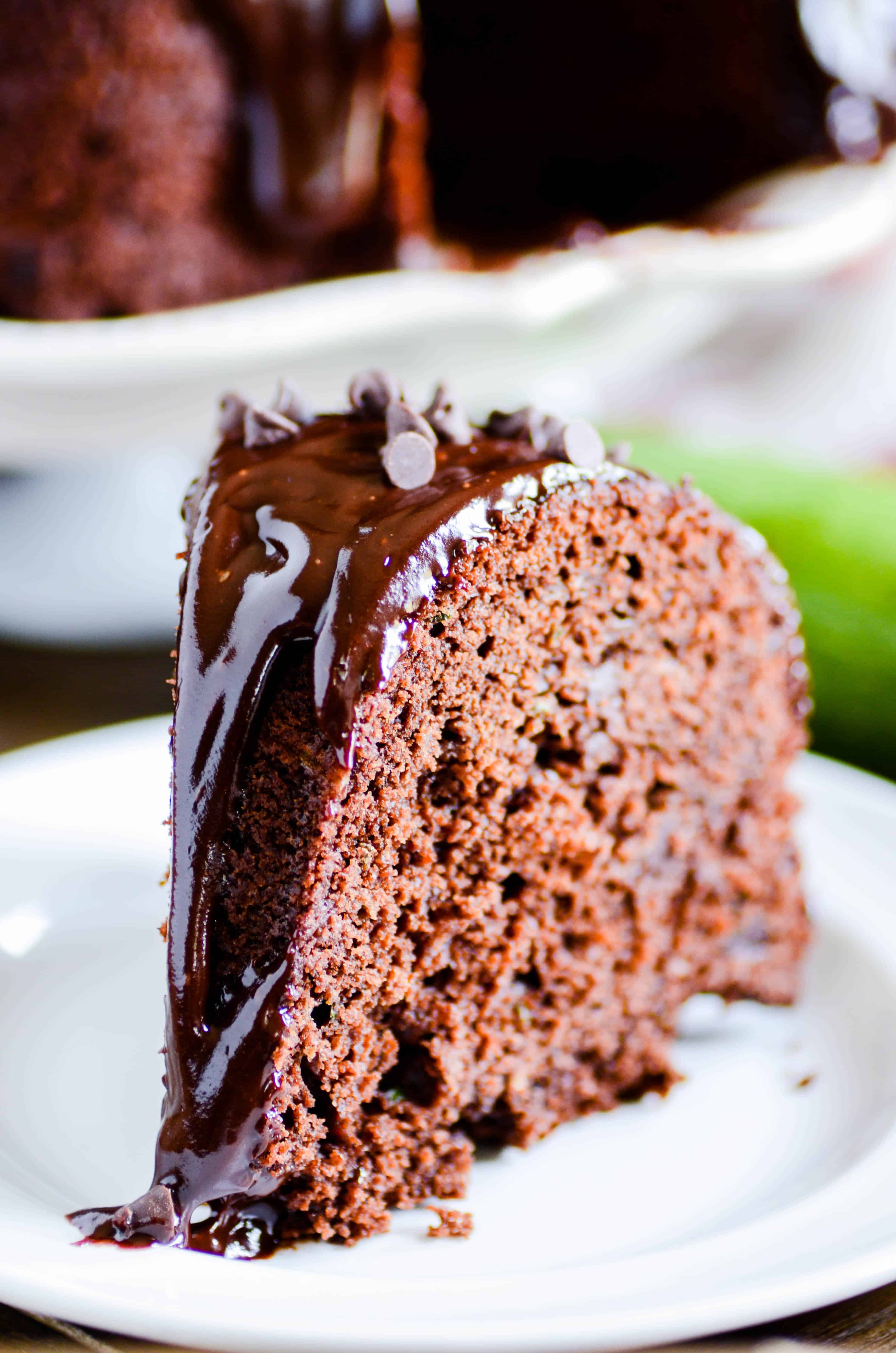 Rich and moist chocolate zucchini cake with chocolate chips and a decadent chocolate ganache on top!