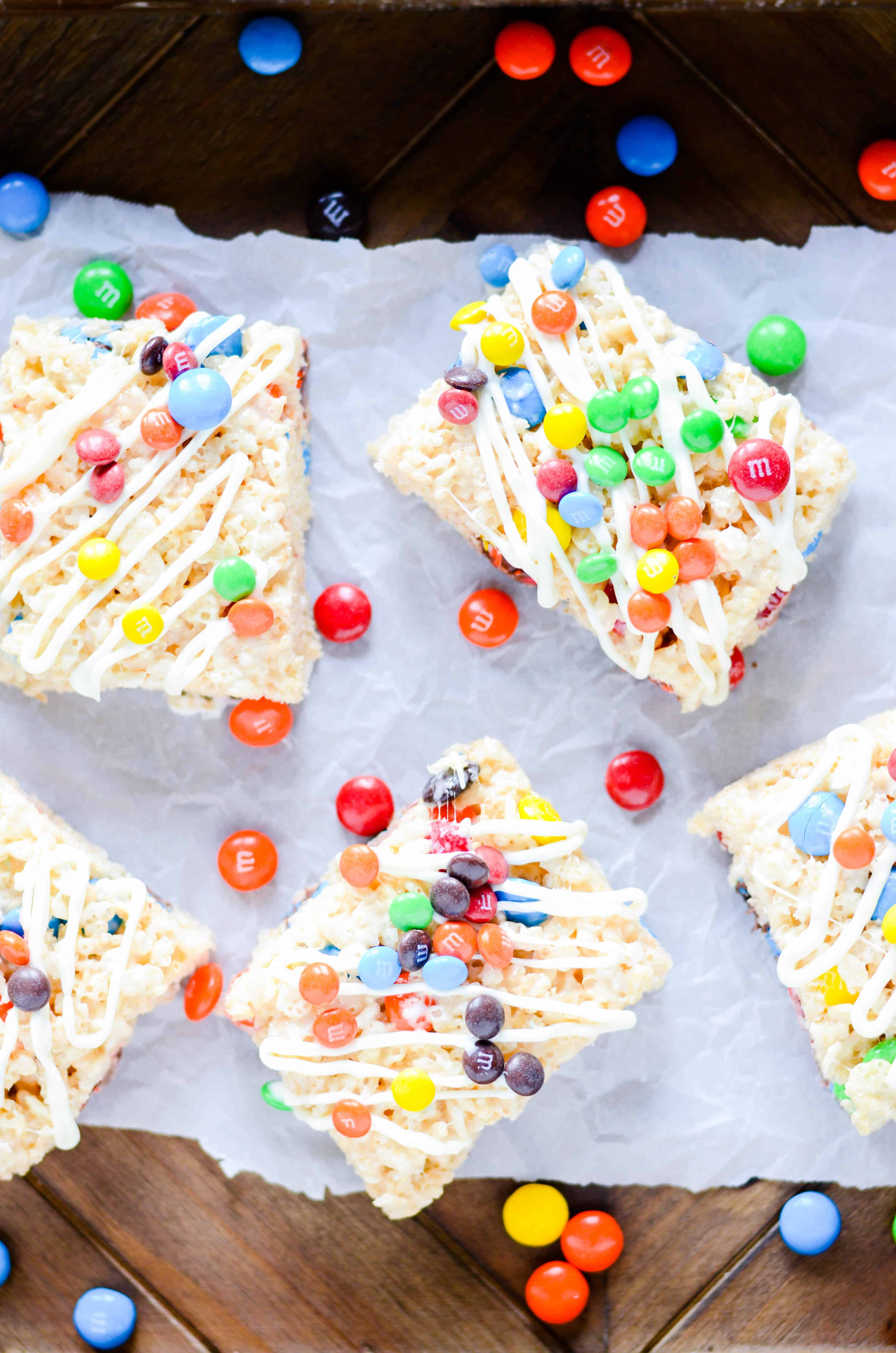 An easy recipe for gooey rice krispie treats with M&MS and a white chocolate drizzle.