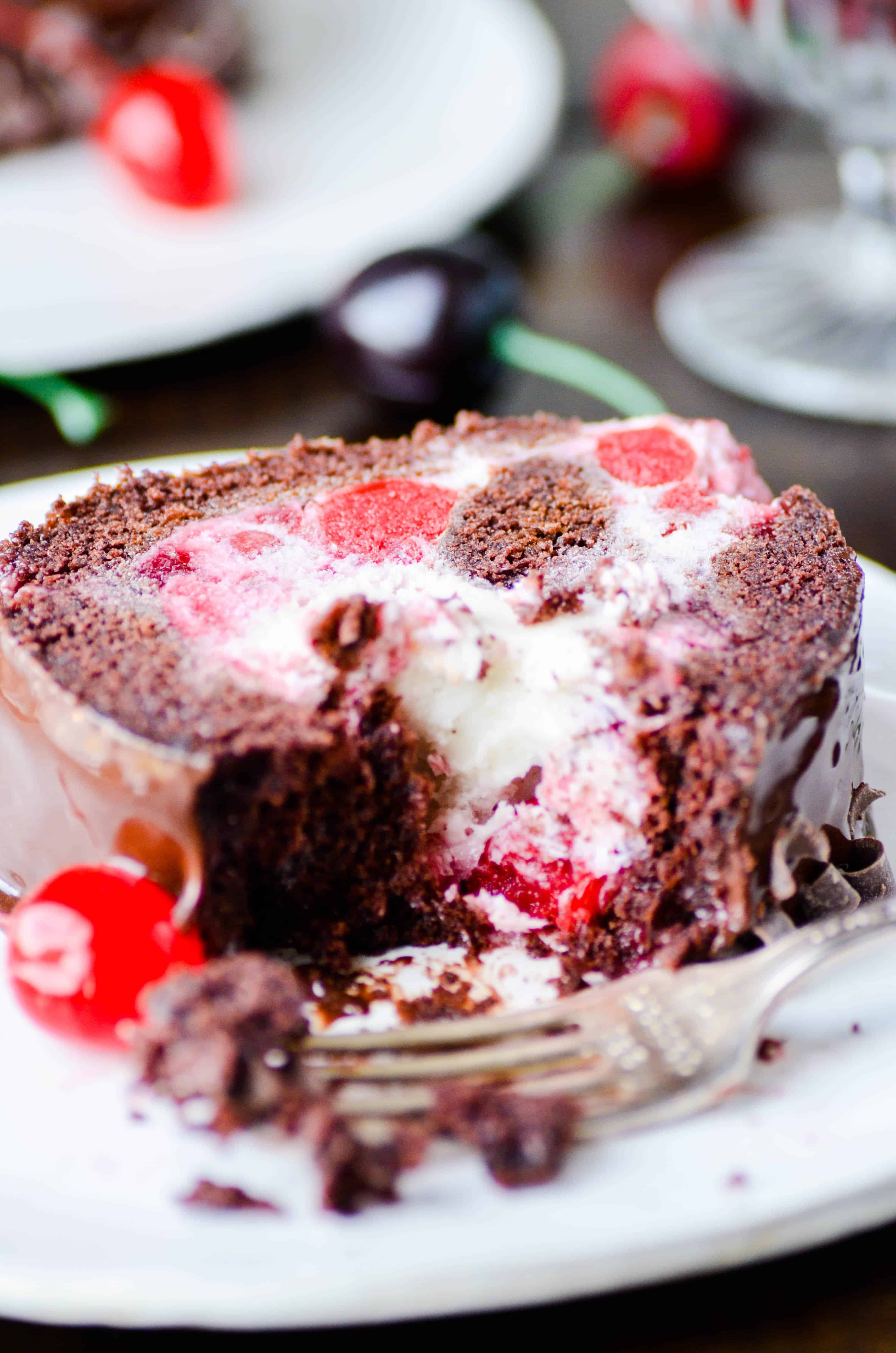 "This Black Forest Ice Cream Cake is a fun ""twist"" on a classic cake. Chocolate cake is layered with vanilla ice cream, cherry pie filling, and topped with chocolate ganache."
