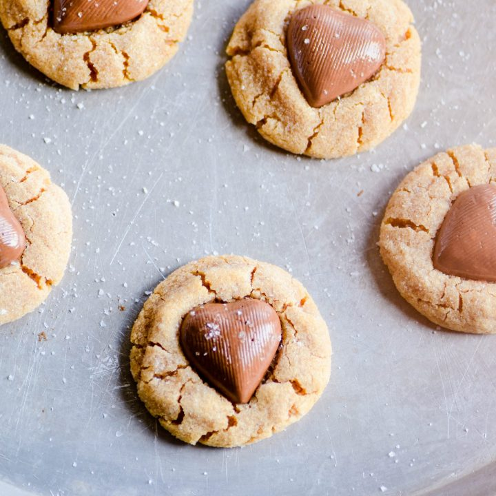 Simple 4-ingredient peanut butter blossoms made with Butterfinger hearts. This my favorite Valentine's day cookie, and we make them every year!