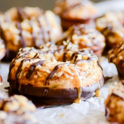 These moist banana bread donuts are baked to perfection, dipped in chocolate, and smothered with coconut and caramel. The banana bread reincarnation of Samoas.