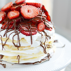 Layers of crepes filled with Nutella, cream, and strawberries. This Nutella Crepe Cake is delicious and pretty easy to make too!