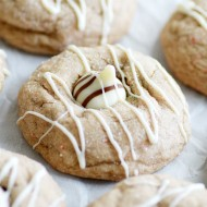 Soft carrot cake cookies stuffed with a Hershey's Hug and drizzled with white chocolate. Soft, delicious, and super easy to make-- a perfect Easter dessert!