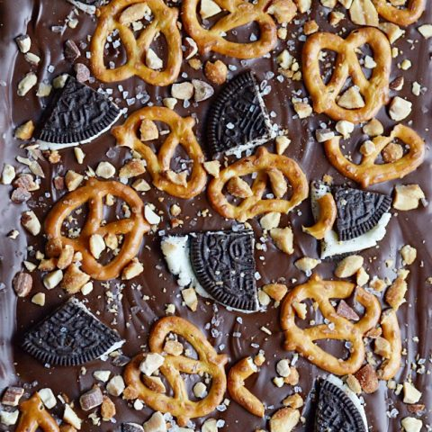 Easy chocolate bark topped with pretzels, Oreos, peanuts, almonds, and sea salt.