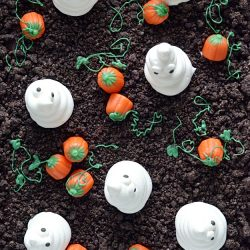 Spooky and cute Halloween cake made with Oreo crumbs, Cool Whip ghosts, and candy corn pumpkins!