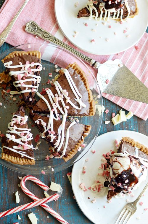 A fudgy peppermint brownie pie topped with white frosting and candy cane bits.