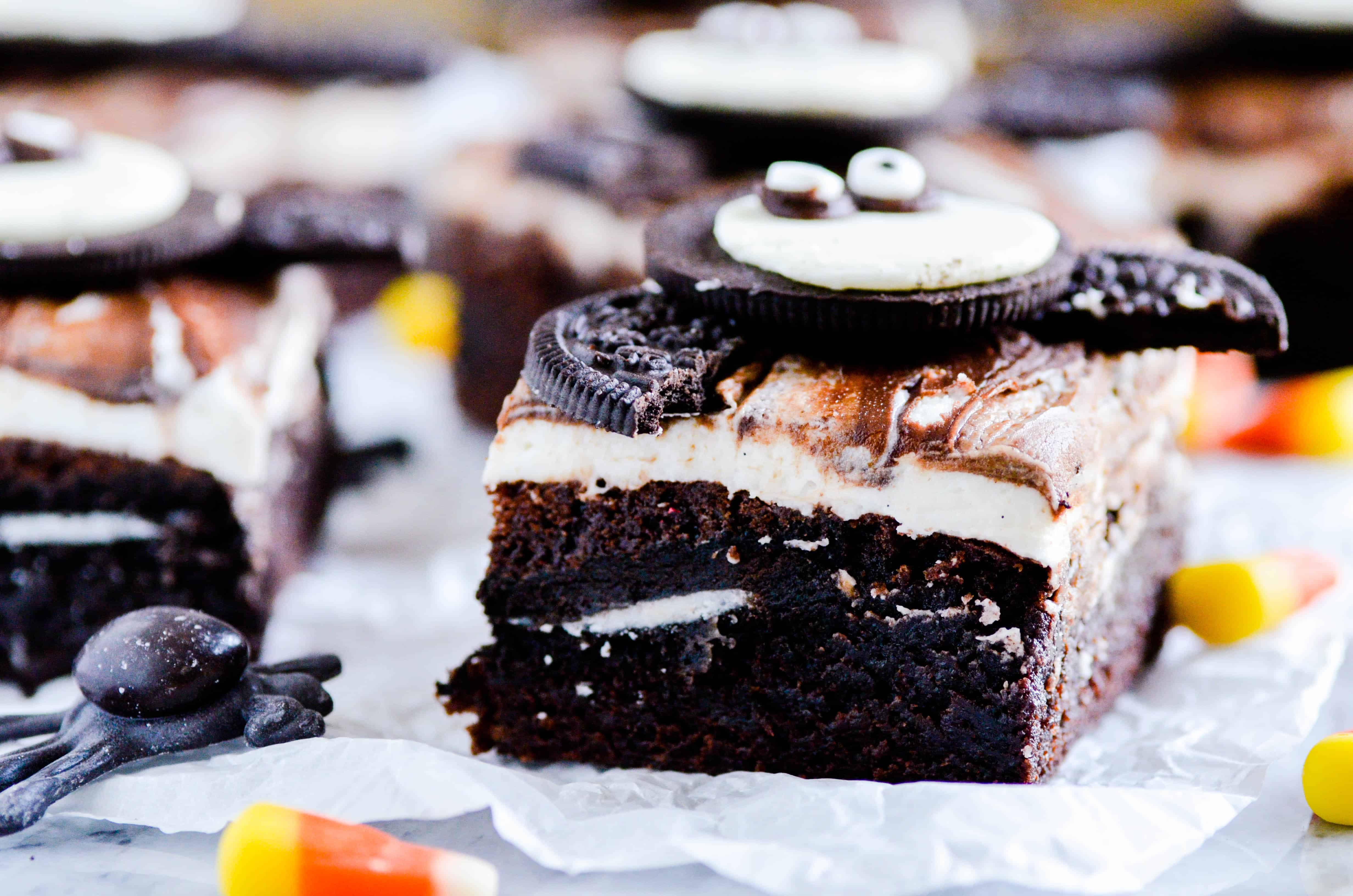 Fudgy brownies with a layer of Oreos in the middle topped with a whipped vanilla buttercream, fudge sauce, and another Oreo for good measure.