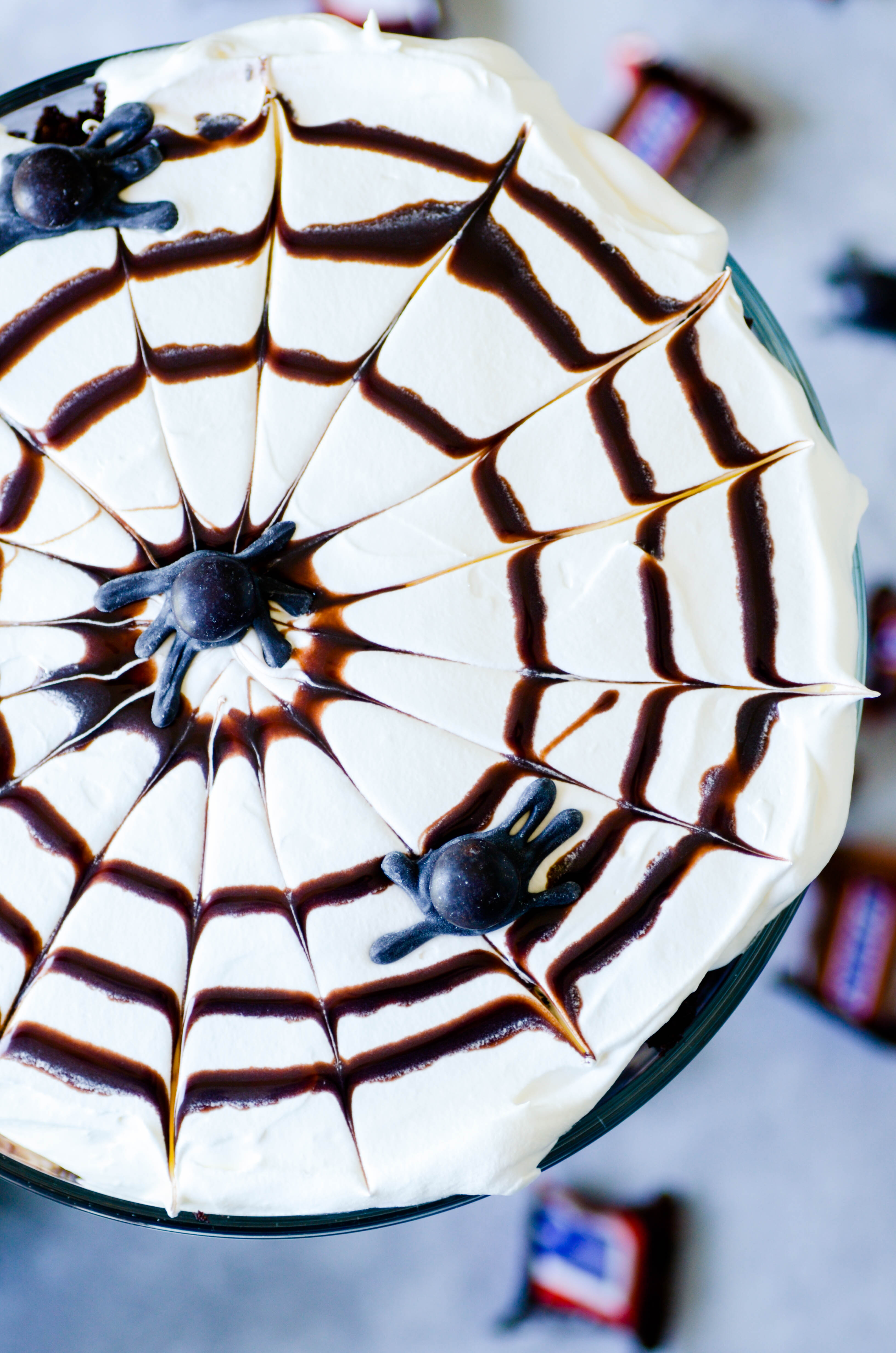 Layers of cake, pudding, whipped cream, and snickers come together in a simple and delicious dessert topped with a chocolate syrup spider web.
