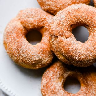 These Pumpkin Cinnamon Sugar Donuts are ready in less than 30 minutes! They are baked instead of fried, which makes this recipe simple enough for a quick and delicious Fall breakfast. The whole family will love the incredible flavor, tender crumb, and sweet cinnamon sugar exterior of these donuts. #recipe #donutpan #easy #baked